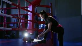 El kickboxer de la muchacha implica cordones antes de entrenar