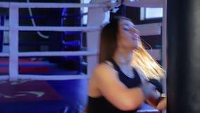 El kickboxer de la muchacha resuelve soplos en la pera en el gimnasio