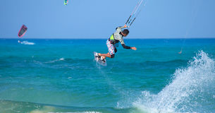 El kitesurfing practicante (el kiteboarding) en la bandera Beac de Corralejo Foto de archivo libre de regalías