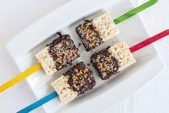 El krispie del arroz se apelmaza en un palillo sumergido en chocolate Imágenes de archivo libres de regalías