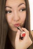 El lápiz labial rojo de aplicación adolescente americano asiático a ella frunció los labios Fotografía de archivo