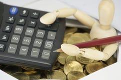 El lápiz que se sostenía simulado de madera con la calculadora ha rodeado por las monedas Imagen de archivo