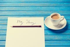 El lápiz y el papel con mi historia redacta cerca de la taza de café foto de archivo libre de regalías