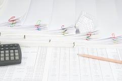 El lápiz y la calculadora tienen casa en la pila del paso de papeleo Imagen de archivo libre de regalías