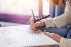 El lápiz y la pluma del dibujo de la mano de la mujer funcionan en el Libro Blanco Foto de archivo libre de regalías