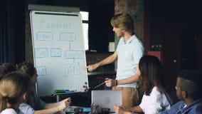 El líder de equipo está haciendo informe en el whiteboard que habla y señalando en la carta, los miembros de equipo están escucha almacen de metraje de vídeo