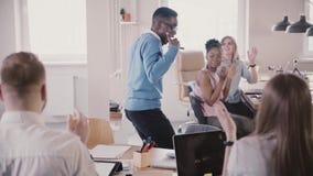 El líder de equipo de sexo masculino afroamericano feliz que hace danza tonta del ganador en la oficina multiétnica del desván, c metrajes