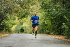 El líder de sexo masculino del corredor de la raza que corre en el parque del otoño, amarillo se va en la tierra Foto de archivo libre de regalías