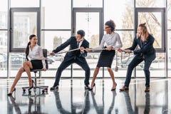 El límite asiático de la empresaria con la cuerda en silla y el negocio multicultural combinan tirando de ella foto de archivo
