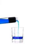 El líquido azul vertió en un vidrio Imágenes de archivo libres de regalías