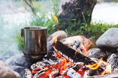 El líquido de ebullición en una taza inoxidable se coloca en las piedras en el fuego Imagen de archivo libre de regalías