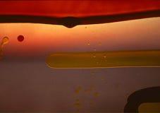 El líquido del polímero gotea el plástico detrás encendido Imagen de archivo libre de regalías