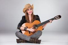 El la muchacha hermosa en un sombrero de vaquero y acústico Imagen de archivo libre de regalías