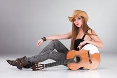 El la muchacha hermosa en un sombrero de vaquero y acústico Fotos de archivo libres de regalías