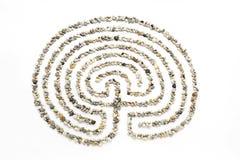 El laberinto en un fondo blanco alineó con las pequeñas piedras del mar Imágenes de archivo libres de regalías