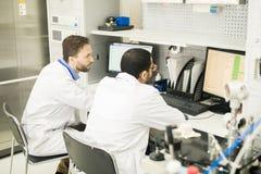 El laboratorio concentrado dirige la discusión de la tabla en línea en el ordenador imagenes de archivo