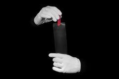 El laboratorio, manos en los guantes blancos sostiene un negro y una película, cuarto oscuro, developmen fotografía de archivo