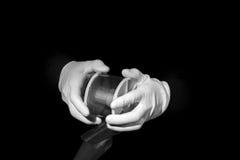 El laboratorio, manos en los guantes blancos sostiene un negro y una película, cuarto oscuro, developmen foto de archivo