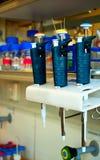 El laboratorio mide con una pipeta la ejecución en un estante Imagen de archivo libre de regalías
