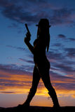 El lado de la mujer de la silueta soporta el arma Imagen de archivo libre de regalías