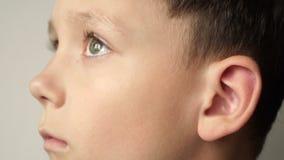 El lado izquierdo de la cara del ` s del niño El oído es primer almacen de video