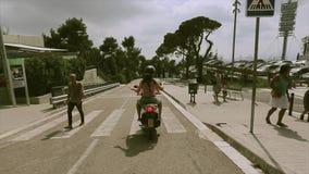 El lado trasero de la gente en cascos monta en las vespas en el camino Manos de la onda de la muchacha Gente traveling Viaje almacen de metraje de vídeo