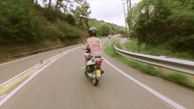El lado trasero de muchachas en cascos monta en las vespas en el camino entre las colinas verdes traveling Viaje metrajes