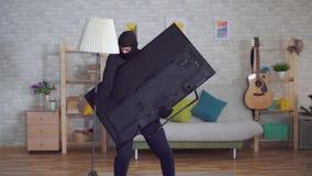 El ladrón anónimo en una máscara del pasamontañas roba una televisión en la casa almacen de metraje de vídeo