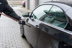 El ladrón con los guantes intenta abrir un coche fotos de archivo