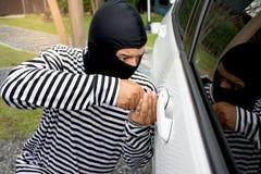 El ladrón del hombre con un pasamontañas en su cabeza que intenta romperse en el coche Él utiliza un destornillador fotos de archivo