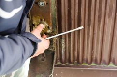 El ladrón destruyó la cerradura en la puerta vieja del metal foto de archivo