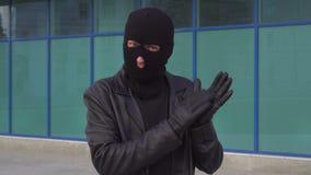 El ladrón o el ladrón criminal admirado del hombre en máscara está aplaudiendo almacen de video