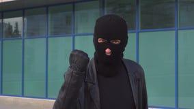 El ladrón o el ladrón criminal del hombre en máscara amenaza alguien con su puño y está haciendo una advertencia almacen de metraje de vídeo