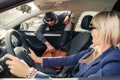 El ladrón roba el bolso de la mujer mientras que ella se está sentando en un coche imagenes de archivo