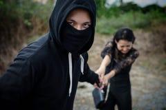 El ladrón roba smartphone de la víctima en el prado Foto de archivo