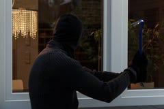 El ladrón rompe el vidrio foto de archivo