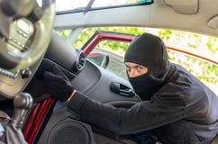 El ladrón rompe la puerta en el coche Fotografía de archivo