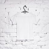 El ladrillo blanqueó la pared con la camiseta blanca en la suspensión Fotos de archivo