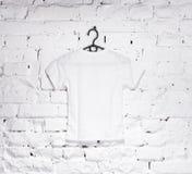 El ladrillo blanqueó la pared con la camiseta blanca en la suspensión Imágenes de archivo libres de regalías