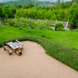 El ladrillo pavimentó el patio con muebles cómodos del patio con las butacas rústicas y un taburete rodeado por el jardín, opinió Fotografía de archivo