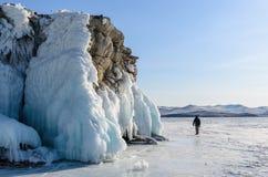 El lago Baikal se cubre con hielo y la nieve, frío fuerte, despeja densamente el hielo azul Caída de los carámbanos de las rocas  foto de archivo libre de regalías