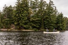 El lago canada Ontario de dos pares de los ríos en una canoa Canoes en el parque nacional del Algonquin del agua Imagen de archivo libre de regalías
