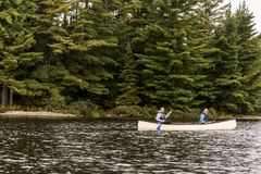 El lago canada Ontario de dos pares de los ríos en una canoa Canoes en el parque nacional del Algonquin del agua imagenes de archivo