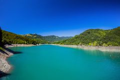 El lago de la montaña con agua verde debajo de un cielo claro azul Foto de archivo