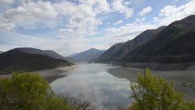 El lago es rodeado por las montañas verdes en el fondo de nubes y del cielo azul Depósito de Zhinvali, río Aragvi, Georgia, Cauca metrajes
