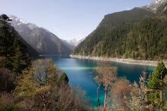 El lago hermoso del color y las montañas circundantes Imagen de archivo