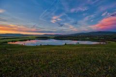 El lago rodeó las colinas y los prados, cielo rojo-amarillo-azul Imagenes de archivo
