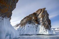 El lago se cubre con una capa gruesa de hielo Historia del hielo Roca de piedra que se pega hacia fuera de debajo las pilas de hi fotografía de archivo libre de regalías
