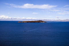 El Lago Titicaca. A boat going between islands on Lake Titicaca in Bolivia Stock Photo