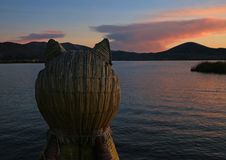 El lago Titicaca en la opinión de la puesta del sol del Totora Reed Boat con la proa formada puma, Puno, Perú foto de archivo libre de regalías